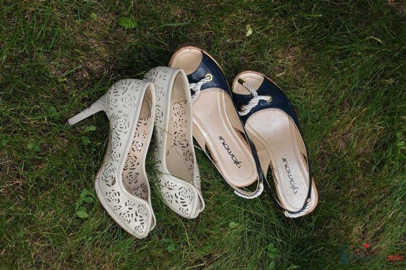 Белые с перфорацией туфли на высоком каблуке, рядом темно синее