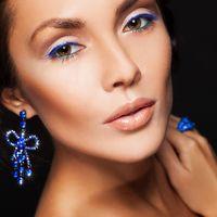 Яркий макияж невесты с ярко-синими стрелками и длинные серьги-банты с подвесками из кристаллов оттенка электрик.