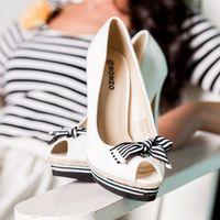 Открытые белые туфли peep toe bow для  невесты в морском стиле стоят на белом подлокотнике кресла возле невесты