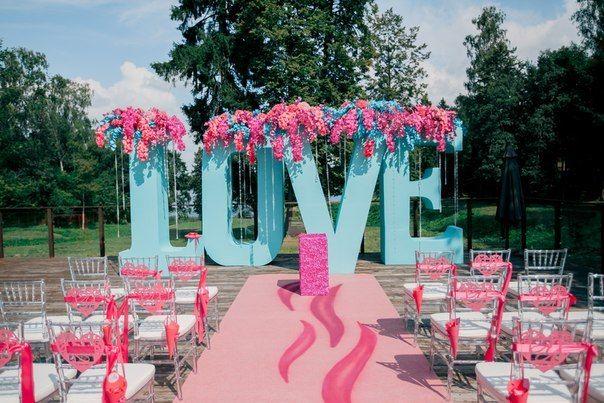 Стулья для гостей на выездной церемонии, украшенные розовой тканью, на фоне объемных голубых букв в розовых цветах - фото 2763025 Добрый Фей - организация свадьбы