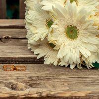 Букет невесты из белых гербер и обручальные кольца