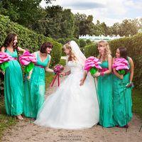 Невеста в белом пышном платье с корсетом и подружки в одинаковых зеленых платьях с V-образным вырезом без рукава розовыми поясами держат розовые розы в парке