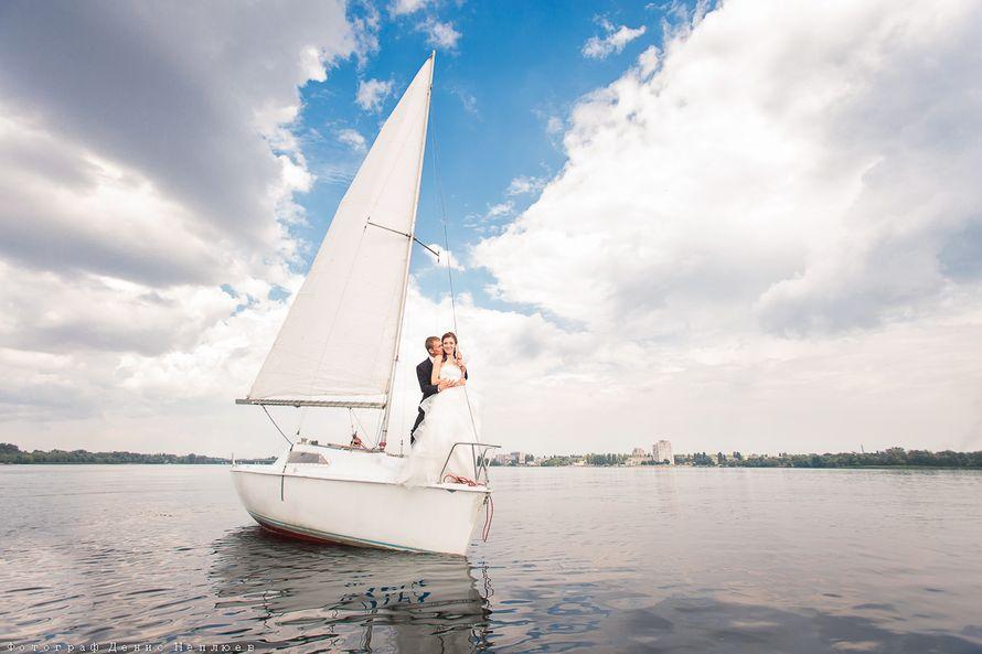 Жених и невеста, прислонившись друг к другу, стоят на палубе яхты на фоне водоема - фото 3650795 Свадебный фотограф Денис Неплюев