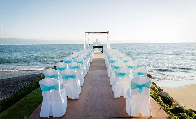 На пляже стоит свадебная беседка, украшенная белой тканью, перед ней стулья в белых чехлах, подвязанные бирюзовыми лентами, - фото 3380227 Holiday Vibes Photo фотосессии в Мексике