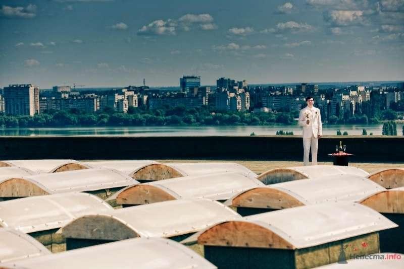 Жених в белом костюме стоит на фоне большого города - фото 49435 Свадебные аксессуары by Оксана Karamelnaya