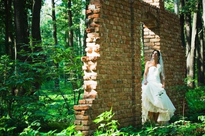 Невеста в белом длинном платье стоит у кирпичной стены в лесу - фото 49523 Свадебные аксессуары by Оксана Karamelnaya