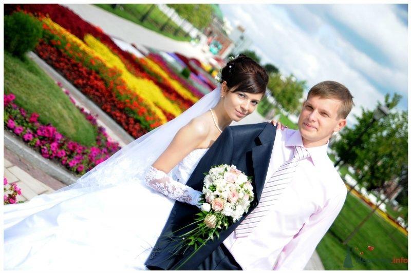 Жених и невеста стоят, прислонившись друг к другу, на фоне зелени и