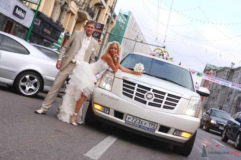 Белый Кадилак, украшенный стойкой из колец на фоне городских улиц, рядом с молодой парой. - фото 51774 barbie