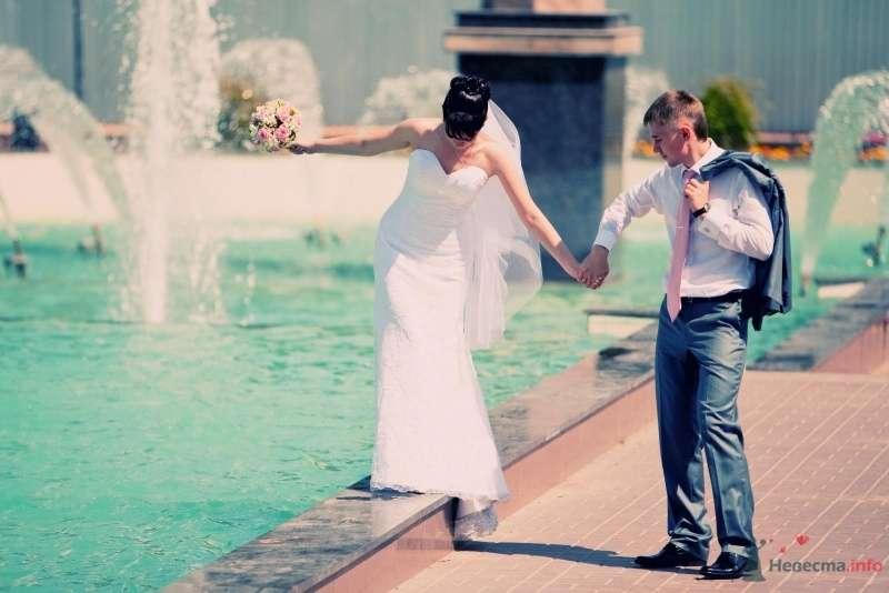 Жених и невеста, взявшись за руки, идут возле фонтана - фото 43490 Santei
