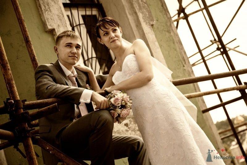 Жених и невеста стоят, прислонившись друг к другу, на фоне  здания