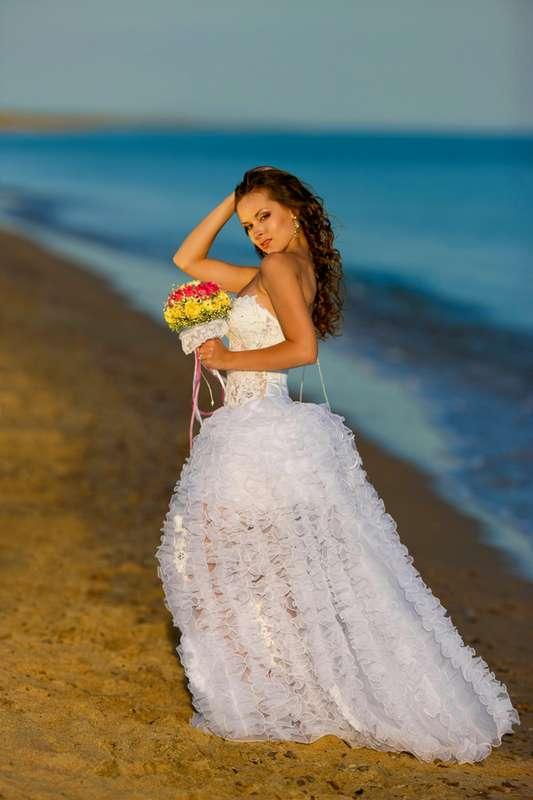 Невеста в красивом ажурном пышном белом платье держит в руках яркий букет стоя на фоне морского берега - фото 542984 Фотограф Николай Хорьков