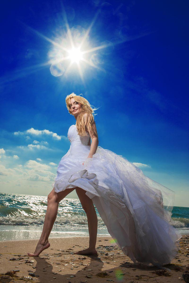 Невеста в белом пышном платье с корсетом идет по пляжу босиком купаясь в лучах морского солнца - фото 600230 Фотограф Николай Хорьков