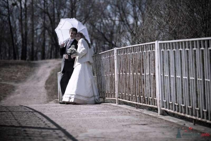 Жених и невеста, прислонившись друг к другу, стоят на фоне деревьев и ограждения - фото 62925 MaRiaRu
