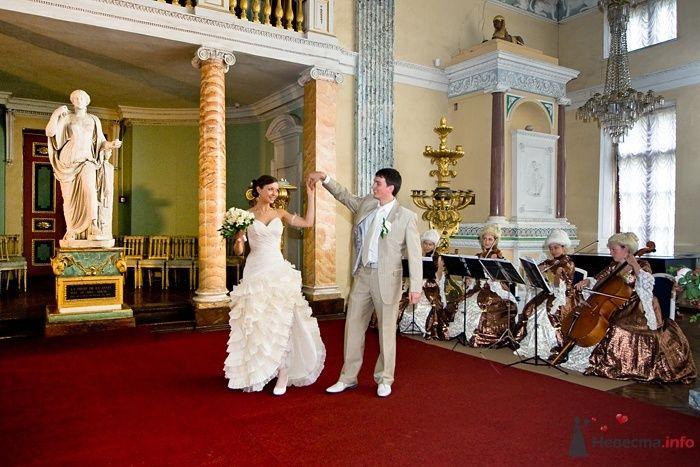Жених и невеста, взявшись за руки, танцуют в большом зале - фото 46639 aiyayai