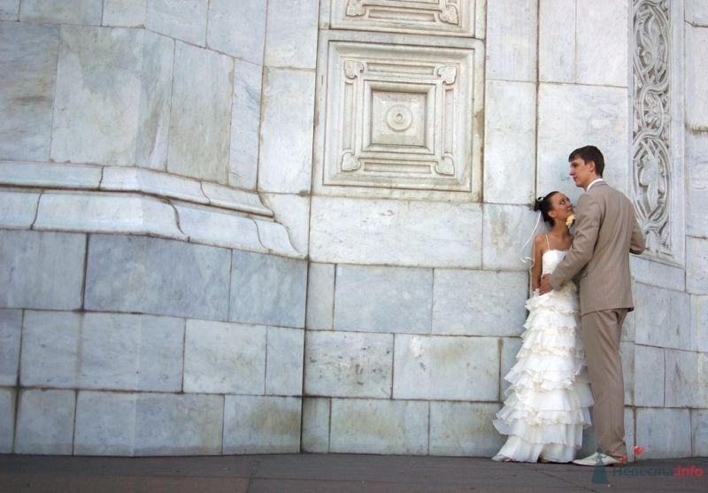 Жених и невеста, прислонившись друг к другу, стоят на фоне белой стены - фото 23973 Fnu