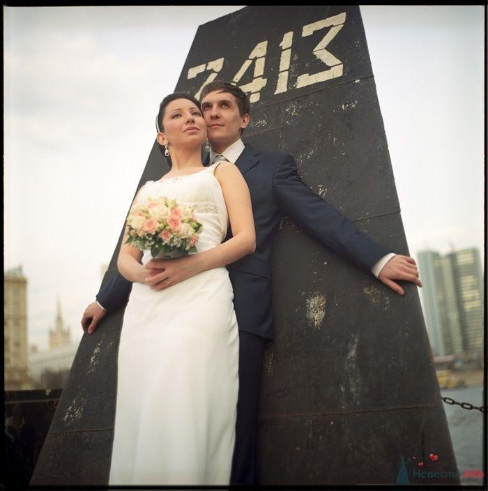 Жених и невеста, прислонившись друг к другу, стоят на фоне монумента