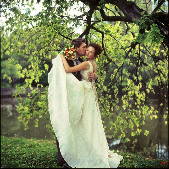 Жених и невеста, прислонившись друг к другу, стоят на фоне зелени у