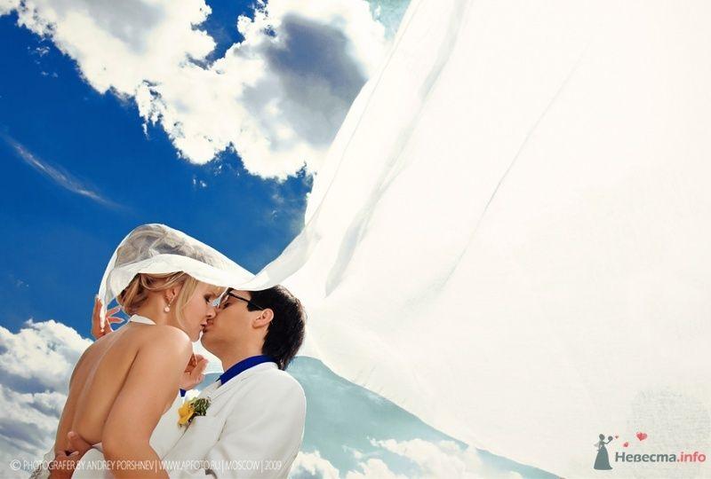 Жених и невеста целуются на фоне облачного неба