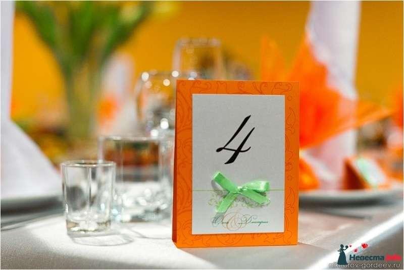 Номерок для стола в виде домика, выполнен из двух цветов дизайнерских бумаг: белого и оранжевого, украшен зелёным бантиком. - фото 294072 Ольга Полякова и Co - ведущая и конферансье