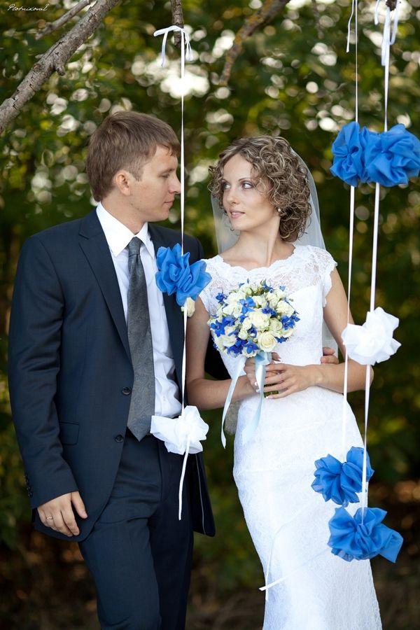Свадебная фотосессия молодоженов с букетом в руках, на фоне висящих синих и белых цветов из ткани - фото 712075 Фотограф Плотникова Елена