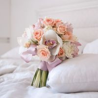 Нежный розово-персиковый букет невесты из орхидей и гиацинтов, завязанный атласной сиреневой лентой