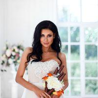 Необычное платье цвета легкой пудры.Юбка платья покрыта легкой фатиновой тканью со шлейфом.Изящное декольте в виде сердечка почеркнет красоту бюста невесты,а опоясывающее талию жемчужное обрамление делает платье еще более шикарным и великолепным