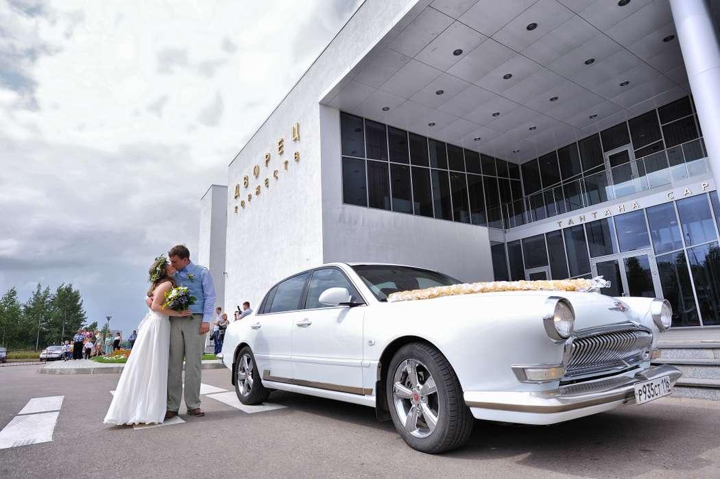 """Белый свадебный """"Chevrolet"""" украшенный лентами на фоне белого здания и счастливых молодоженов. - фото 1682157 Проект """"Автоностальгия"""" - аренда авто"""