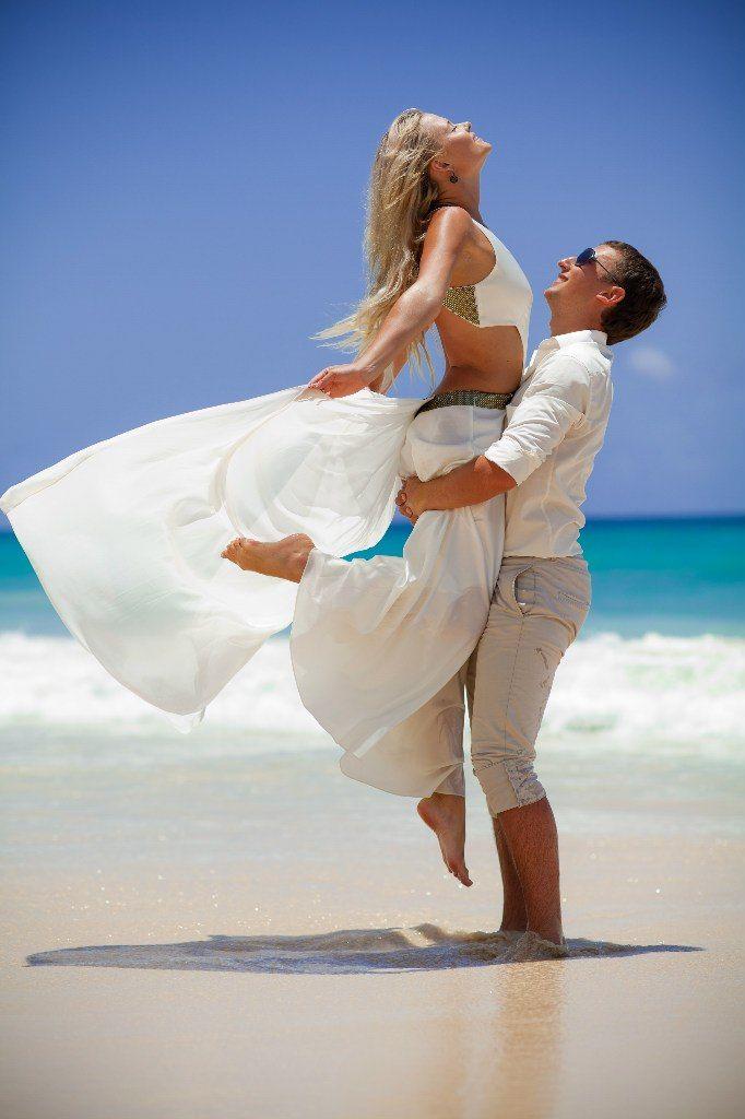 Жених держит на руках невесту стоя на пляже, невеста в белой юбке и топе, жених в бежевых шортах и белой рубашке - фото 545379 Анастасия954
