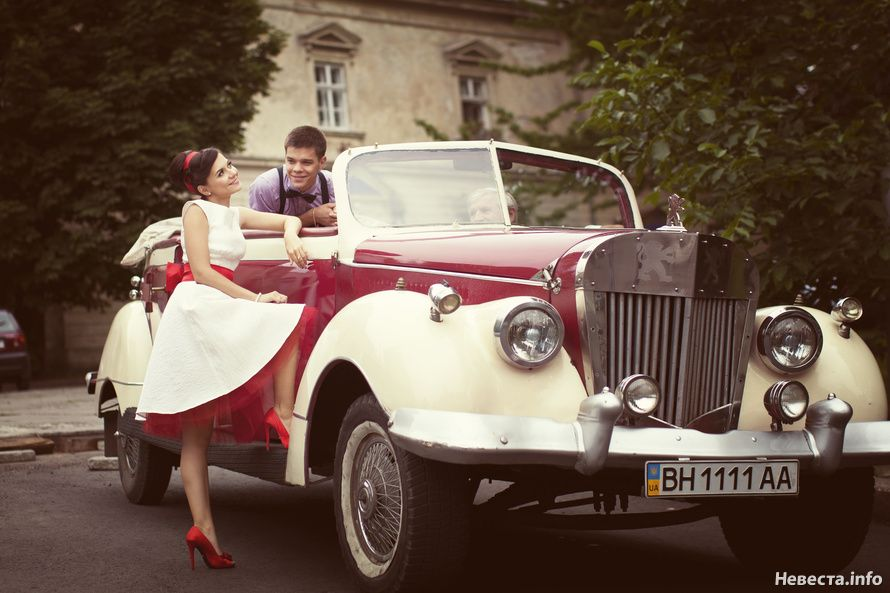 """Красно- белый """"Rolls-Royce"""" на фоне старинного здания и зелени деревьев, рядом с парой молодоженов. - фото 1194867 Angie"""