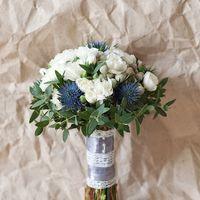 Букет невесты в бело-серо-голубых тонах. Собран из белой гвоздики, голубого эрингиума, серебристой брунии и зелени эвкалипта. Ножка декорирована атласной лентой и кружевом из натурального хлопка.