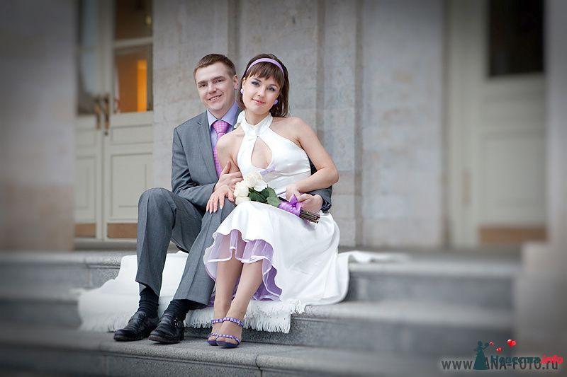 Жених и невеста сидят, прислонившись друг к другу, на ступеньках