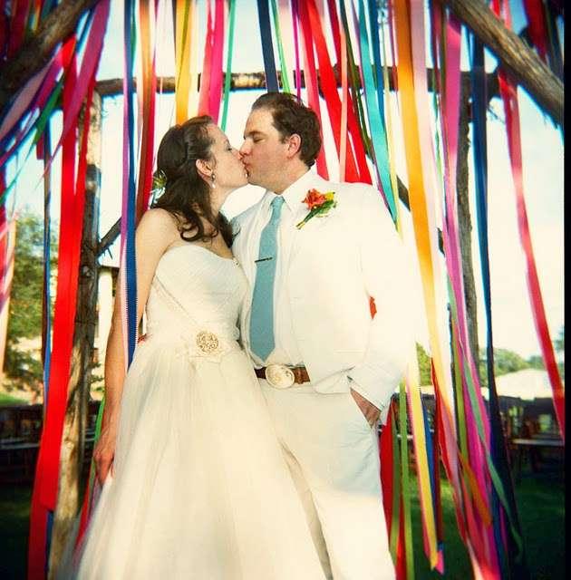 Свадебная арка с ленточной драпировкой, декоративными элементами на фоне молодоженов - фото 833065 Дизайн-студия Ольги Шишловой