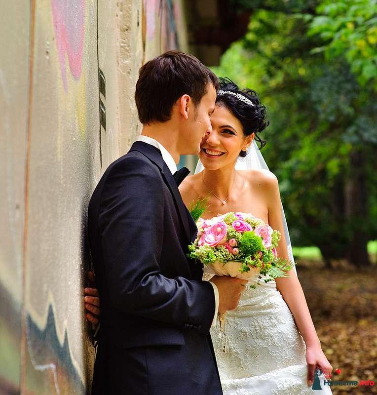 Жених и невеста стоят, прислонившись друг к другу, возле серой стены в парке - фото 103739 Garriy