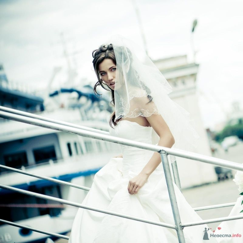 Невеста в белом платье идет по лестнице