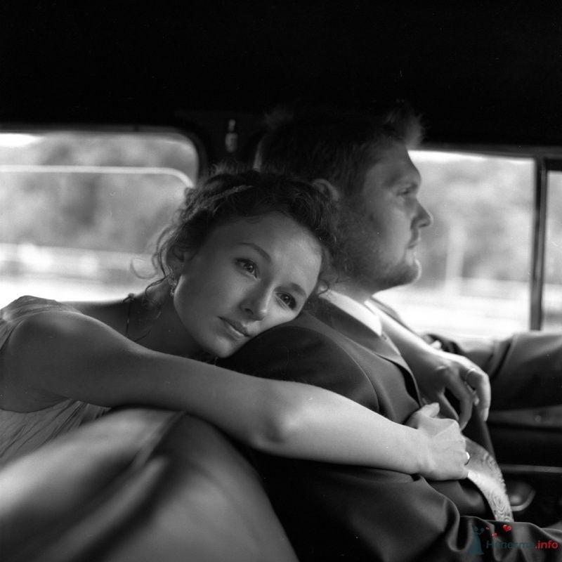 Жених и невеста сидят, прислонившись друг к другу, в машине