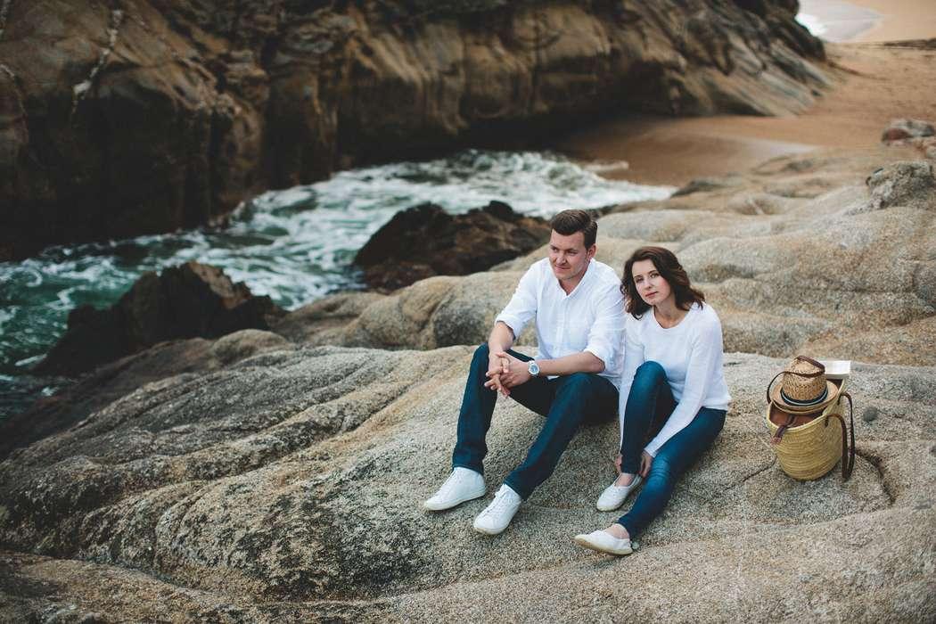 На каменистом берегу сидит влюбленная пара, на них синие брюки и белые рубашки, рядом с ними корзина с продуктами для пикника, - фото 2274986 Фотограф Ксения Пардо