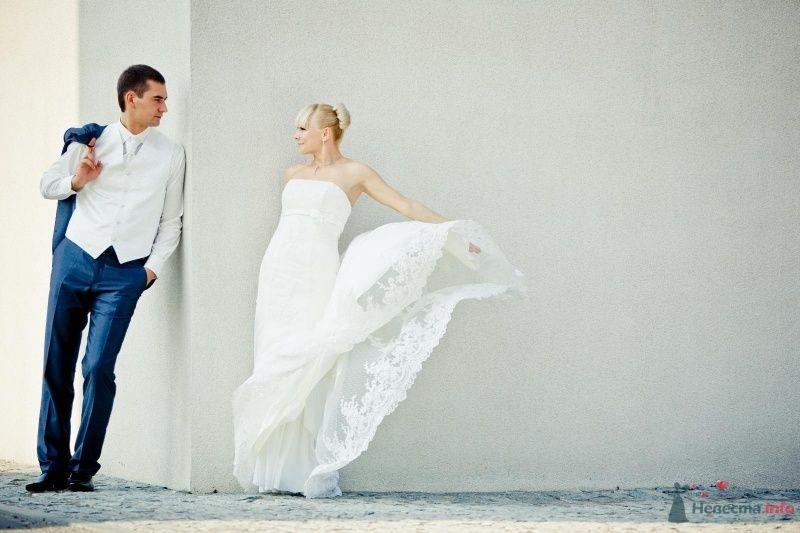 Жених и невеста стоят возле белой стены