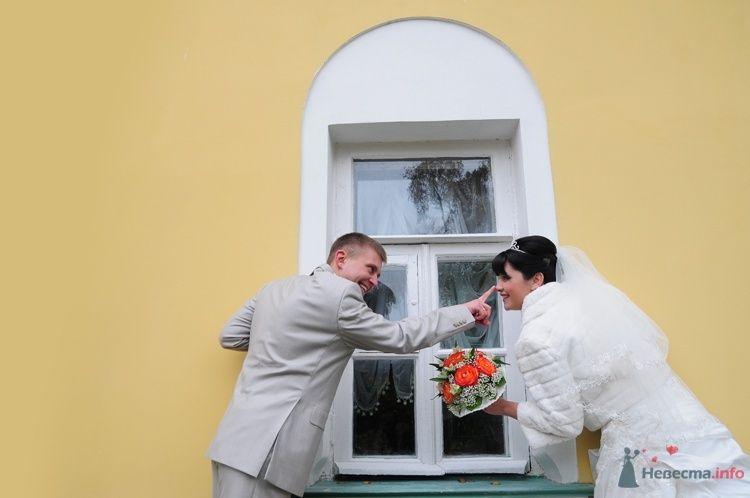Жених и невеста стоят возле окна на улице