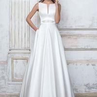 Белоснежное атласное свадебное платье классического кроя с красивым вырезом на груди. Пояс украшает сияющая прозрачными кристаллами пряжка.  Подробности тут: