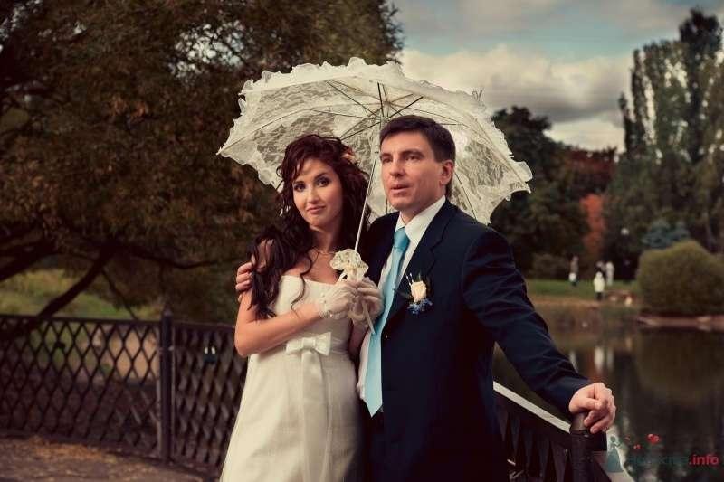 Жених и невеста стоят, прислонившись друг к другу, под белым зонтом - фото 47524 Annuta