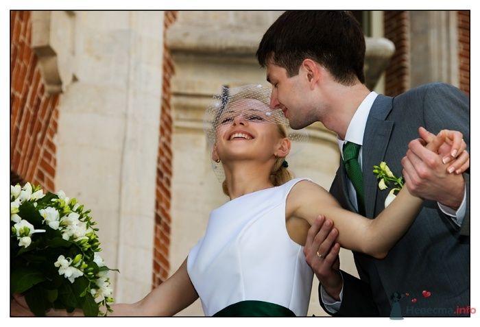 Жених и невеста, прислонившись друг к другу, стоят посреди комнаты