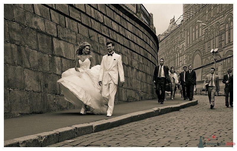 Жених и невеста идут по серой улице города