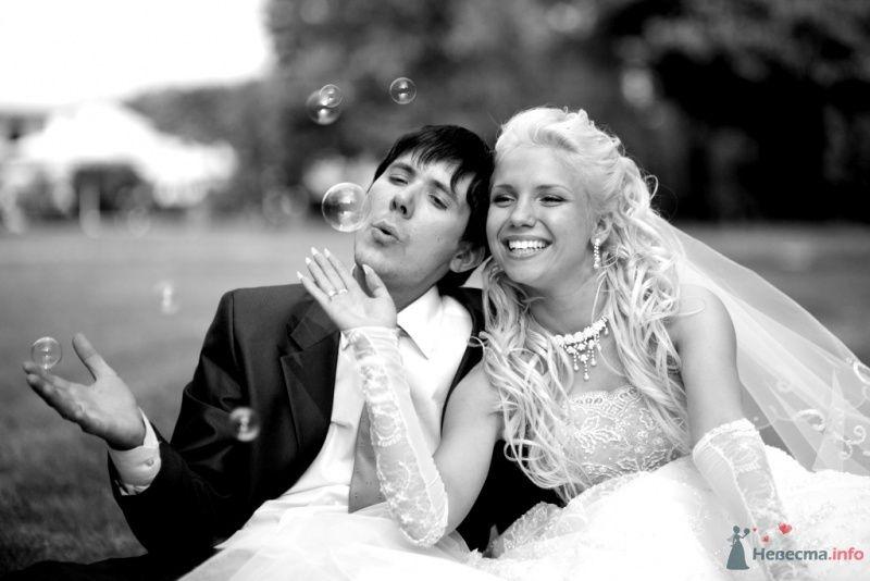 Жених и невеста сидят, прислонившись друг к другу, на улице