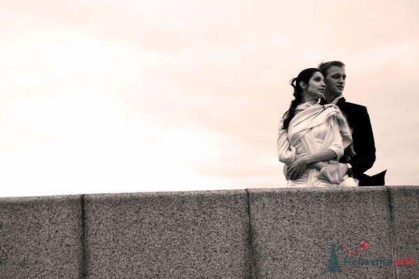 Жених и невеста стоят, прислонившись друг к другу, на фоне ограждения - фото 45620 OlgaTimkina