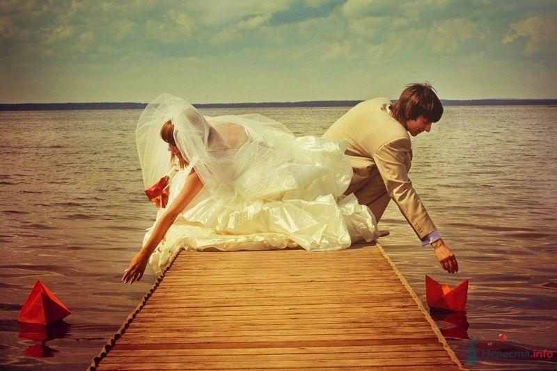 Жених и невеста стоят на пирсе  и опускают бумажных корабликом в воду - фото 61903 yanechka