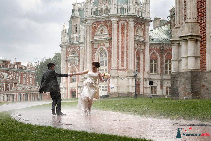 Жених и невеста, взявшись за руки,  кружатся посреди улицы