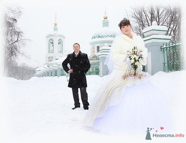 Жених и невеста стоят на заснеженной улице возле белой церкви