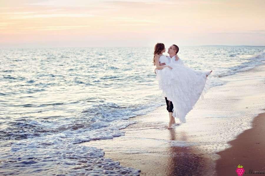 Жених прогуливаясь босиком вдоль пляжа несет на руках свою возлюбленную в белом пышном платье  - фото 891343 Свадебное агентство Малина