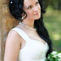 Алена, невеста стоит рядом с колонной на улице рядом с парком