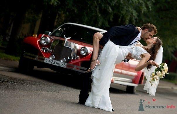 Жених держит на руках невесту возле красной машины на улице